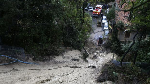 Cars are parked beneath a mudslide after heavy rains caused flooding in southeastern France.