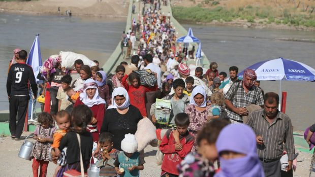 Displaced Iraqi Yazidis cross the Syrian-Iraqi border in  August.