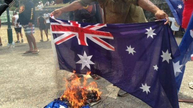 A protester holds the Australian flag over a fire.