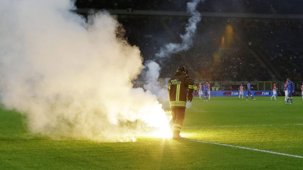 A firefighter removes a flare thrown by Croatia supporters.