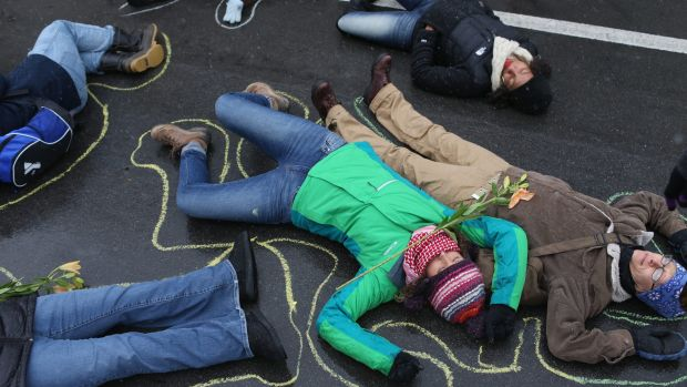 Demonstrators lie on the ground in a mock death protest on Monday of the August shooting death of Michael Brown by a ...