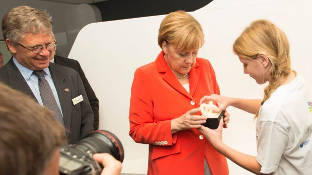 German Chancellor Angela Merkel tries out Esther Schulz's mood light as NICTA CEO Hugh Durrant-Whyte looks on.