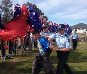 Police arrest a man during a political demonstration outside Parliament House during Chinese president Xi Jinping's visit.