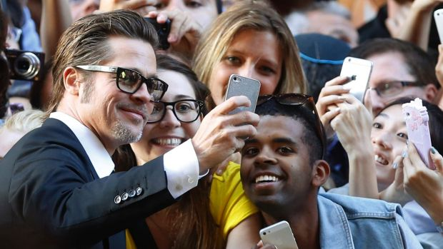 Brad Pitt takes time for selfies with fans.