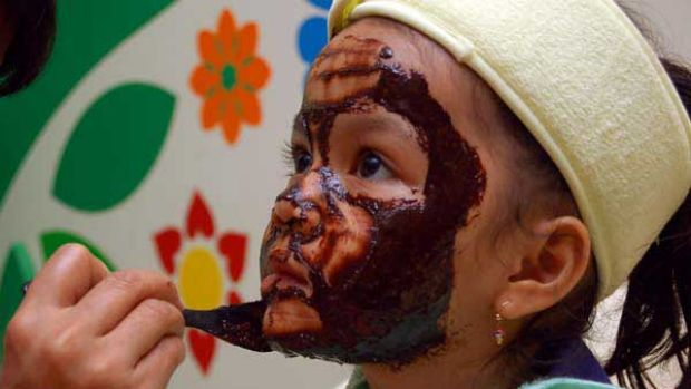 Nadra Rani, 5, patiently sits through a chocolate facial courtesy of her mother, a Jakarta salon manager. <i>Picture: ...