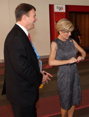 Ms Bishop demonstrates how to button a jacket when getting off a plane with US Ambassador John Berry at the G20 in ...