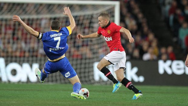 Brett Emerton attempts a lunging tackle against Manchester United at ANZ Stadium in 2013.