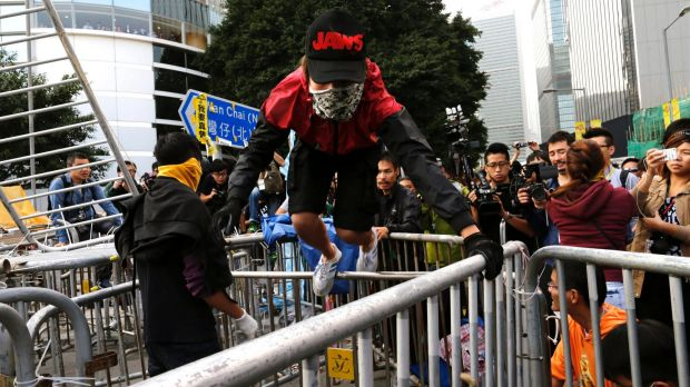 Masked man: A pro-democracy protester climbs on a barricade after the arrival of bailiffs clearing the protest site.