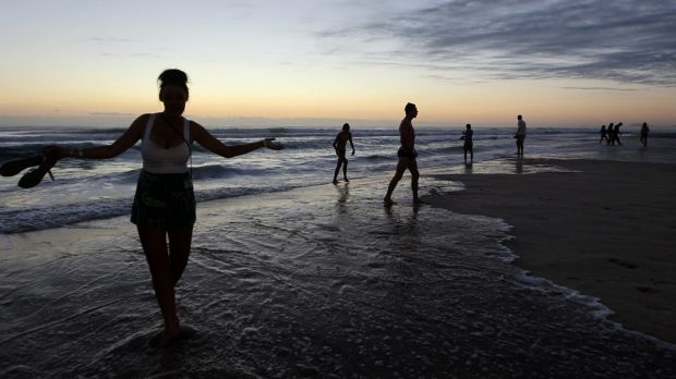Schoolies wait for the sun to rise on the beach at Surfers Paradise.