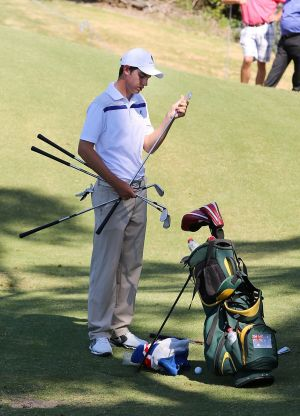 Ryan Ruffels gets his clubs ready at practice.