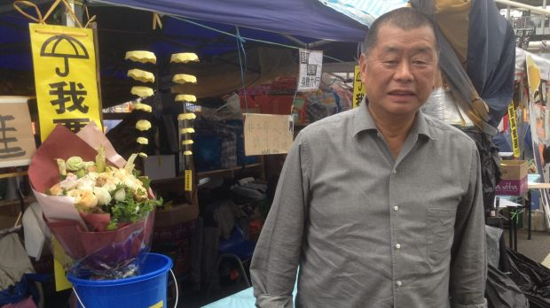 """""""I want genuine universal suffrage"""" reads the umbrella sign at Hong Kong Media magnate Jimmy Lai's tent."""