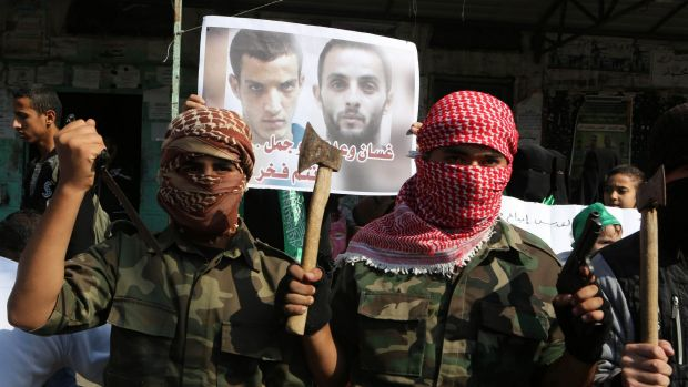 Masked Palestinians hold knives and axes as they celebrate an attack on a Jerusalem synagogue.