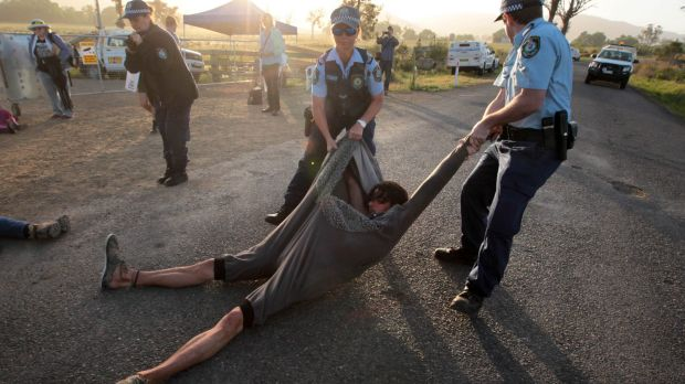 An anti-CSG protester is dragged away near AGL's proposed gas field near Gloucester, last year.