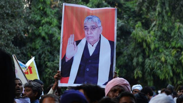 Devotees of Indian self-styled ''godman'' Rampal Maharaj hold a poster of his image during a sit-in protest in Delhi.