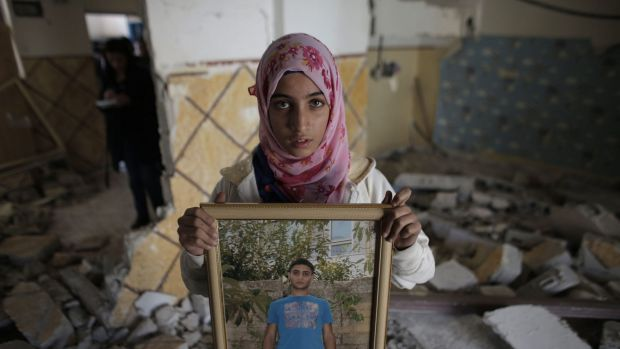 A relative of Abdelrahman Shaludi, a Palestinian who killed two Israelis with his car last month, displays his portrait ...