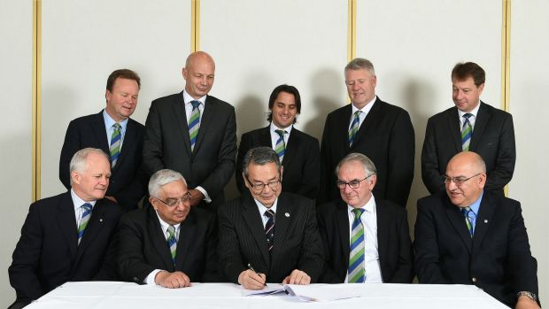 The brains trust: Bill Pulver and co. watch on as Tatsuzo Yabe of the JRFU signs on the dotted line.