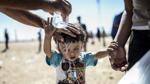 Cooling down: A Syrian Kurd pours water on a child after they crossed the border between Syria and Turkey in September, ...
