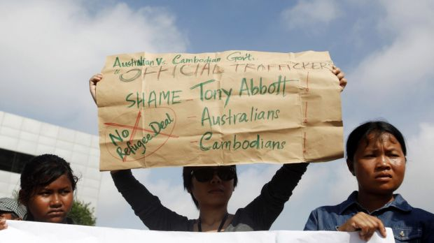 Protesters in Phnom Penh hold signs during a demonstration against Cambodia's plans to resettle intercepted refugees in ...