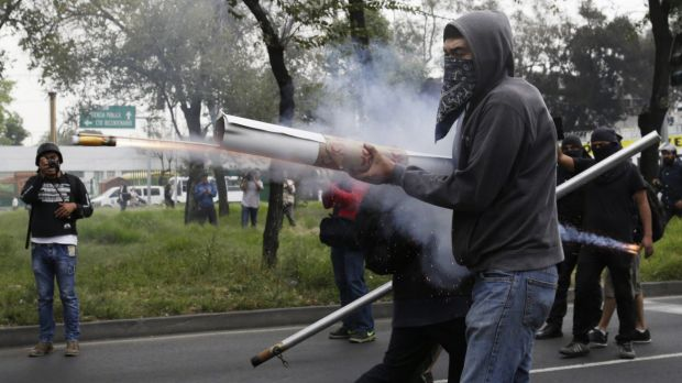 Makeshift weapons: Demonstrators fire fireworks towards riot police during a protest over the missing Ayotzinapa ...