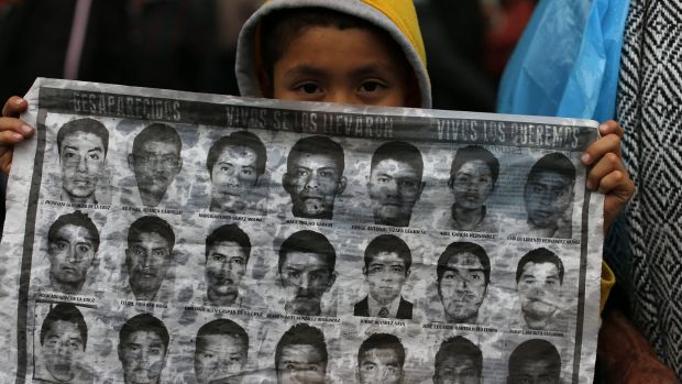Dubious treatment: A boy holds up a sheet of photos showing some of the missing 43 students at the Independence monument ...
