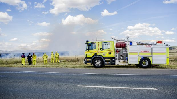 Firefighters extinguish a grass fire near Majura Park on Friday.