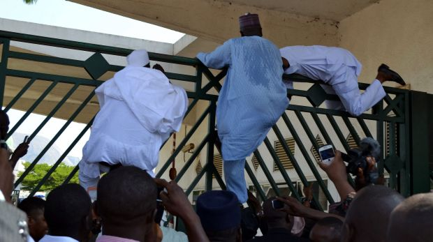 Nigerian Parliament members try to climb the assembly gate to be present for a key security vote.
