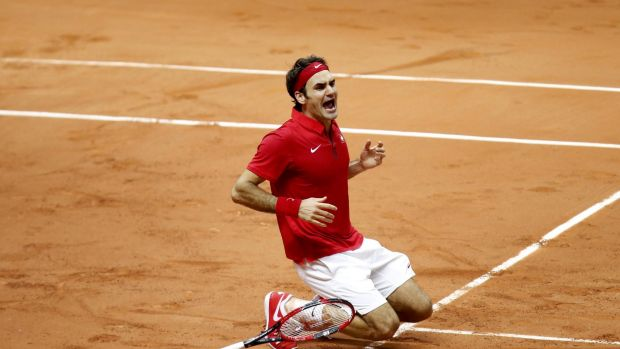Overcome: Roger Federer collapses on the French clay after helping Switzerland claim their first Davis Cup title.