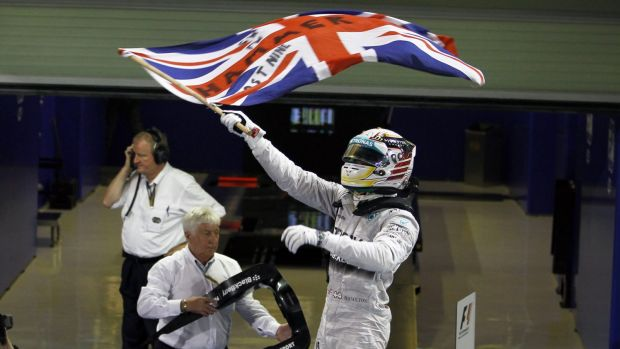 Lewis Hamilton waves the Union flag after winning the Abu Dhabi Grand Prix to claim the F1 title.