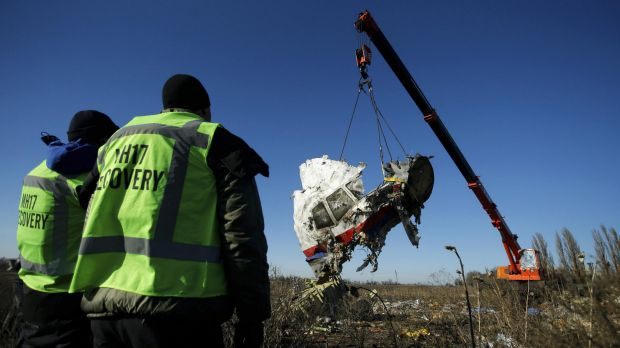 Investigators watch as a piece of wreckage from the Malaysia Airlines flight MH17 is recovered near the village of ...