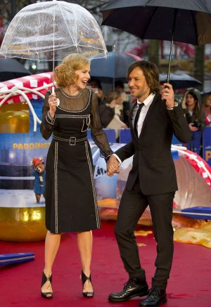 Under cover: Nicole Kidman and Keith Urban on the rain-drenched red carpet in London on Sunday.