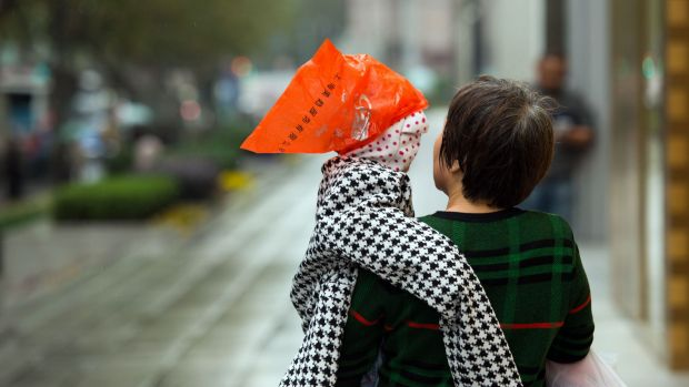 A woman carries a boy in Shanghai. China's one-child policy has led to a gender imbalance with there being fewer females ...