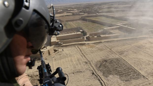An Afghan helicopter door gunner looks out during a flight carrying journalists in the Yahya Khail district following ...