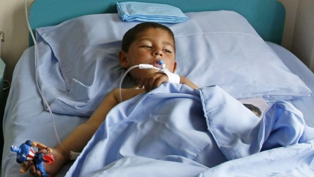 A boy receives treatment at a military hospital in Kabul after being wounded during a suicide attack at a volleyball ...