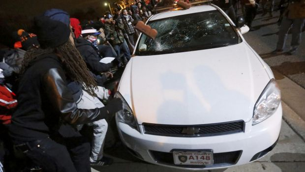 Protesters vandalise a car outside the Ferguson Police Department in Ferguson.