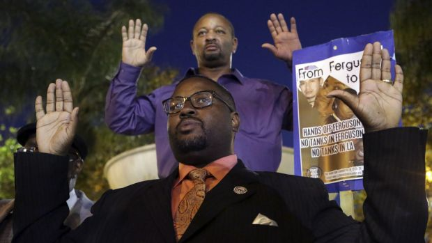 Reverend K.W. Tulloss and community activist Najee Ali hold up their arms during a demonstration in Los Angeles ...