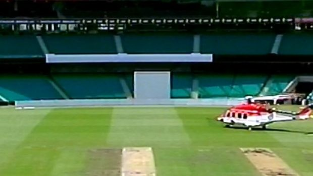 A chopper arrives on the SCG with a doctor to help Hughes.