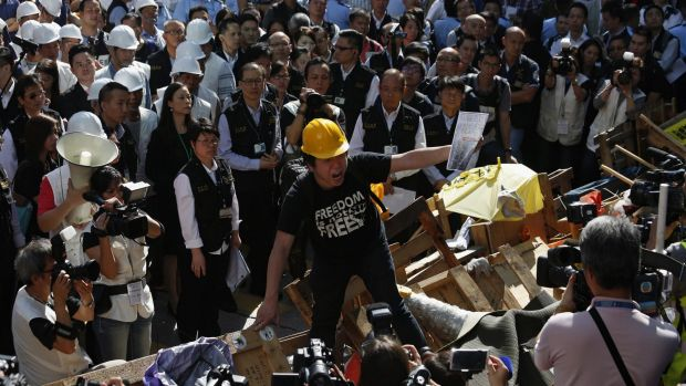 A pro-democracy protester denounces a statement from a lawyer prior to the removal of the barricades blocking Argyle ...