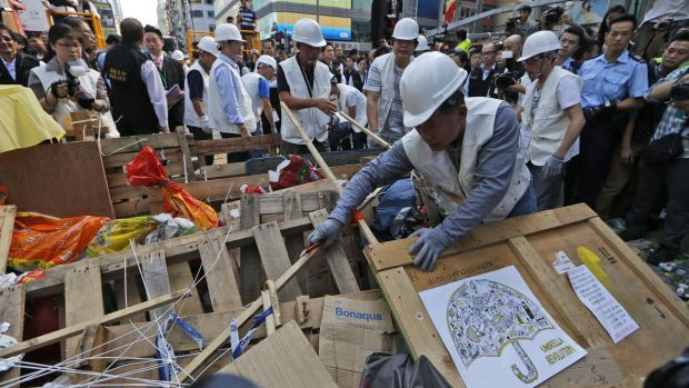 Workers begin clearing away barricades in compliance with a court order at the Mong Kok site.