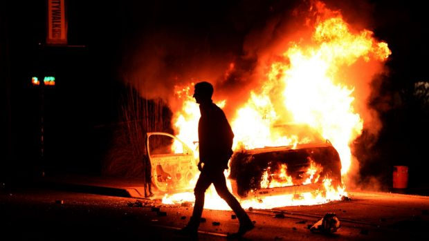 A burning police vehicle during clashes in Ferguson.