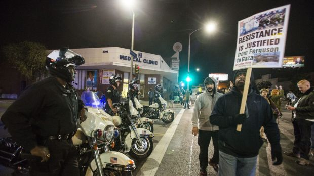 Police officers keep watch as demonstrators block an intersection  during a rally.