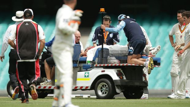 Phil Hughes is placed on a medicab at the SCG on Tuesday.