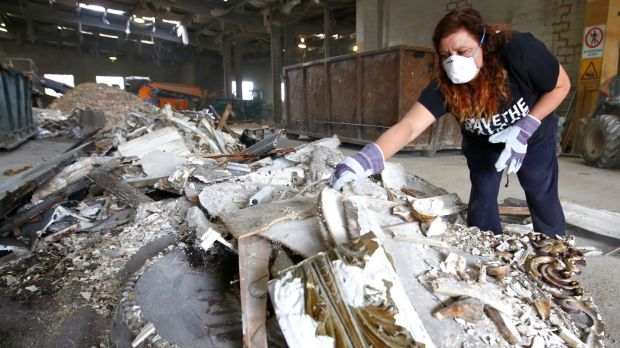 Activists fossick through a skip containing material taken from the Palace last week.