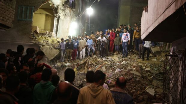 Cairo residents stand on the remains of the collapsed building.