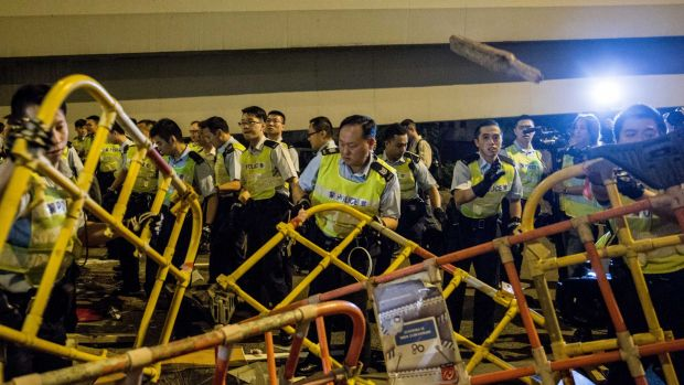 Opening the road: Police clear barriers in a main road after pro-democracy protesters attempted to use them to build a ...
