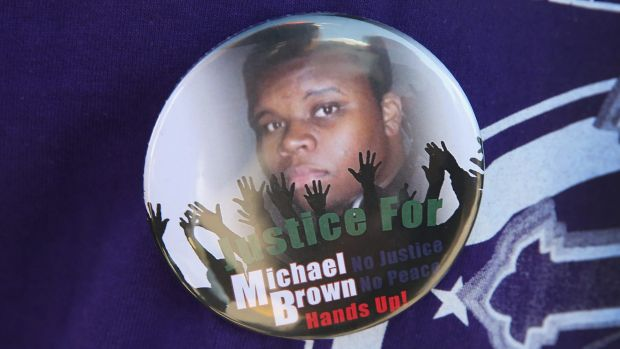 A resident wears a button featuring a picture of teenager Michael Brown, who was killed by police officer Darren Wilson ...