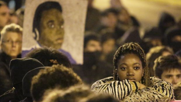 Paying respects: Demonstrators mark a moment of silence following the grand jury decision at a protest in Seattle, ...