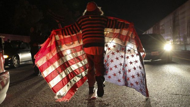 Querying justice system: A protester carrying an upside-down flag marches past cars on a highway in Oakland, California.