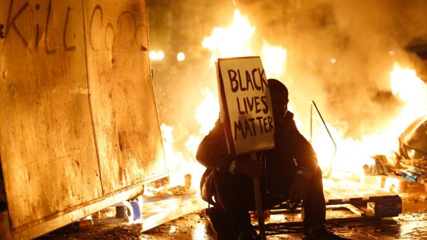 Ferguson burning: A demonstrator sits in front of a street fire during a Ferguson demonstration in Oakland, California.