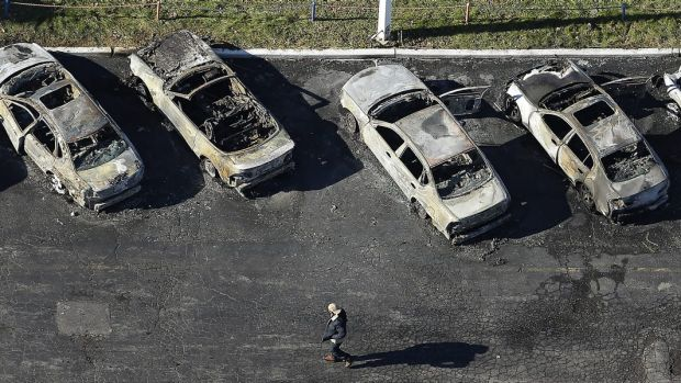 A man walks past a row of gutted cars at a dealership in Dellwood, Missouri, after rioting followed the grand jury's ...