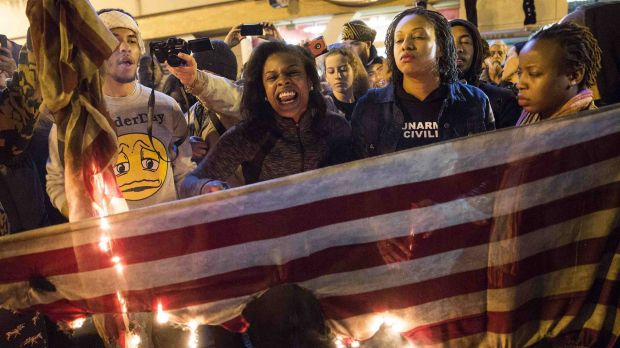 """Demonstrators burn the American flag during a """"Justice for Mike Brown"""" march in Washington."""